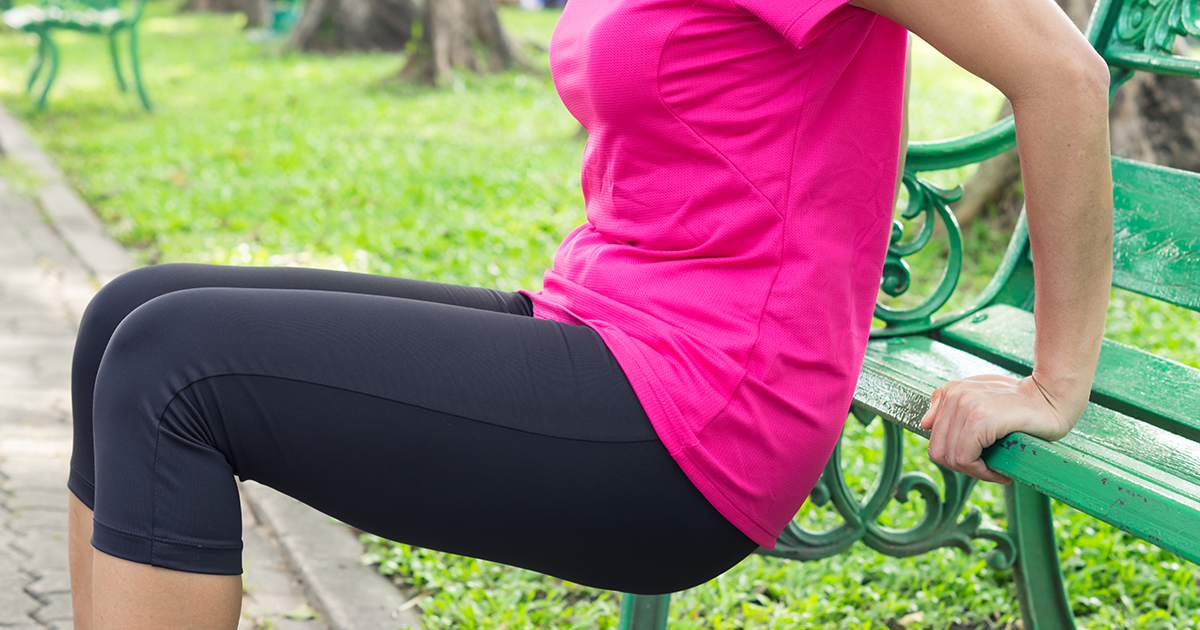 woman doing tricep dips on outdoor bench